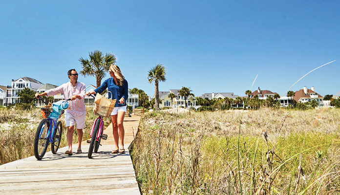 Ac couple walks to the beach on Wild Dunes in the Isle of Palms.